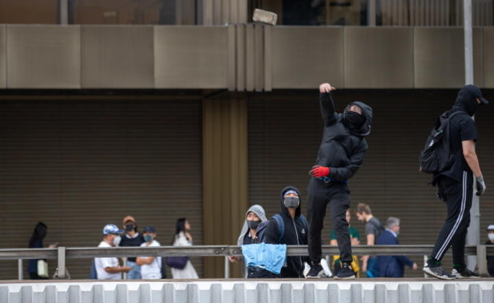 A protester throws a brick on to a road to stop traffic in the business district / autor: EPA/JEROME FAVRE / EPA / PAP